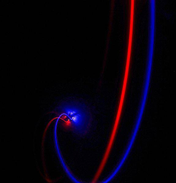 Red_and_blue_light_drone_flying_inside_a_room_in_the_dark.jpg