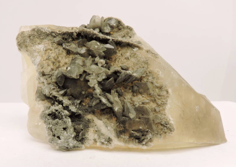 Large calcite crystal with a layer of small calcites, phantoms and an inclusion from China - cabinet size