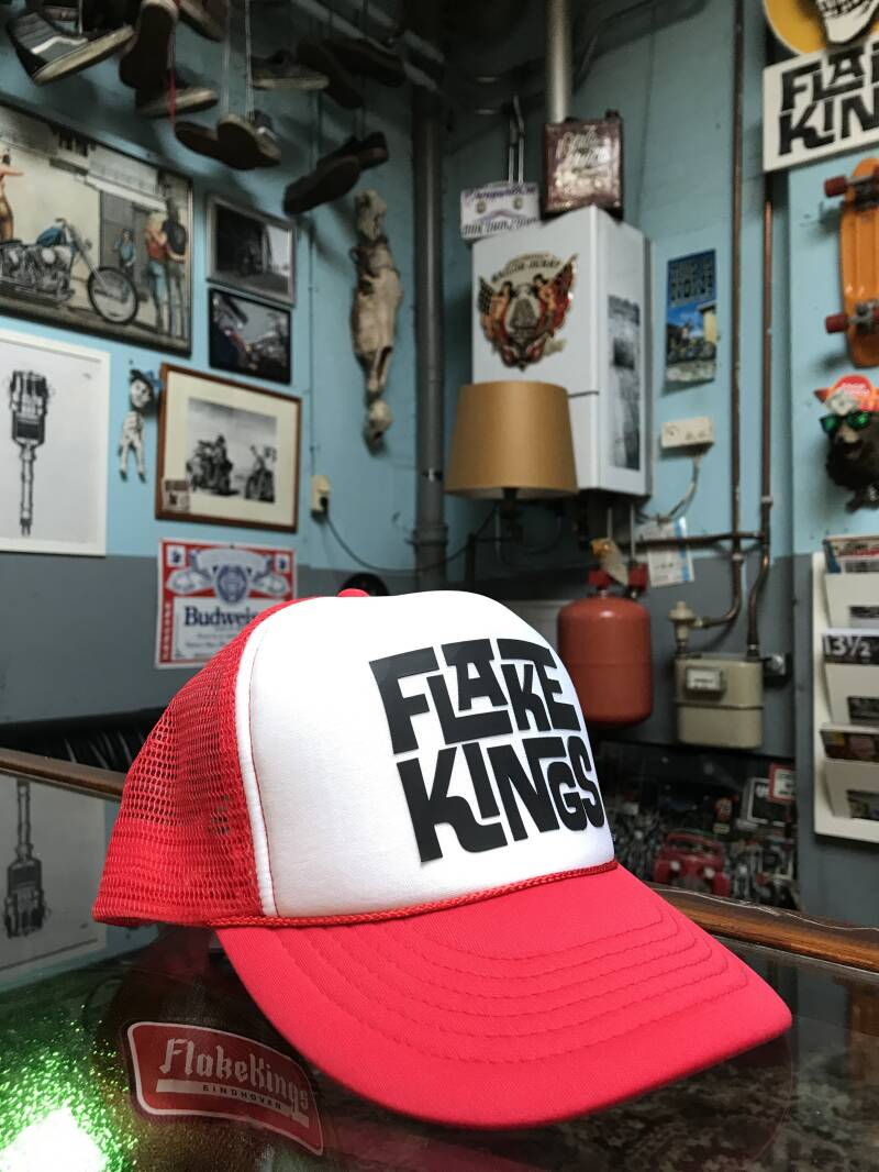 FlakeKings black typo print, snap back, red / white trucker cap.