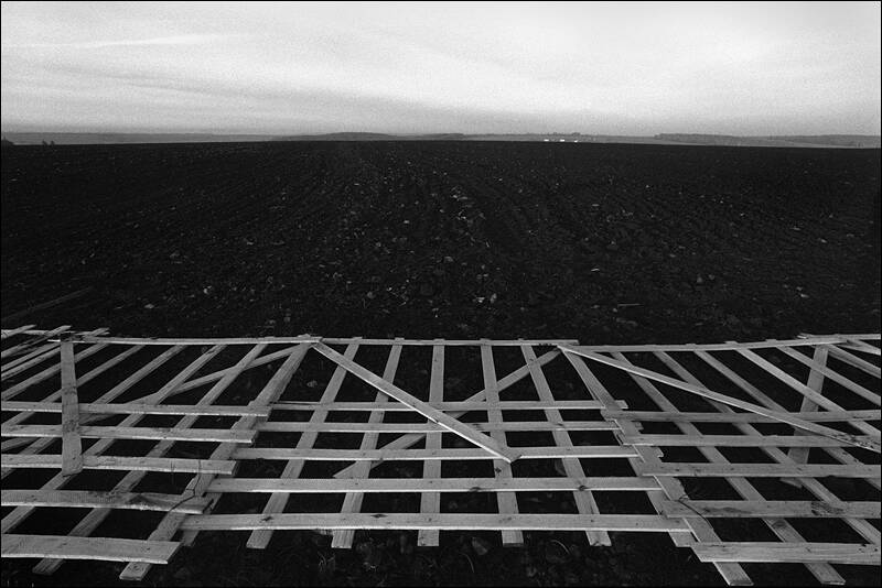 Installation of a wind shelter fence on a arable land along the highway