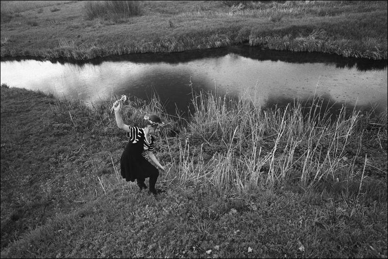 The girl collecting flowers on a river slope for weaving of wreaths