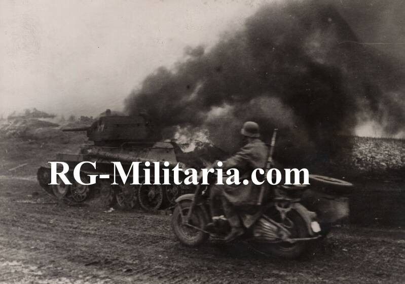 Press photo - SS motor in front of a burning Soviet T-34/76 tank (1944)