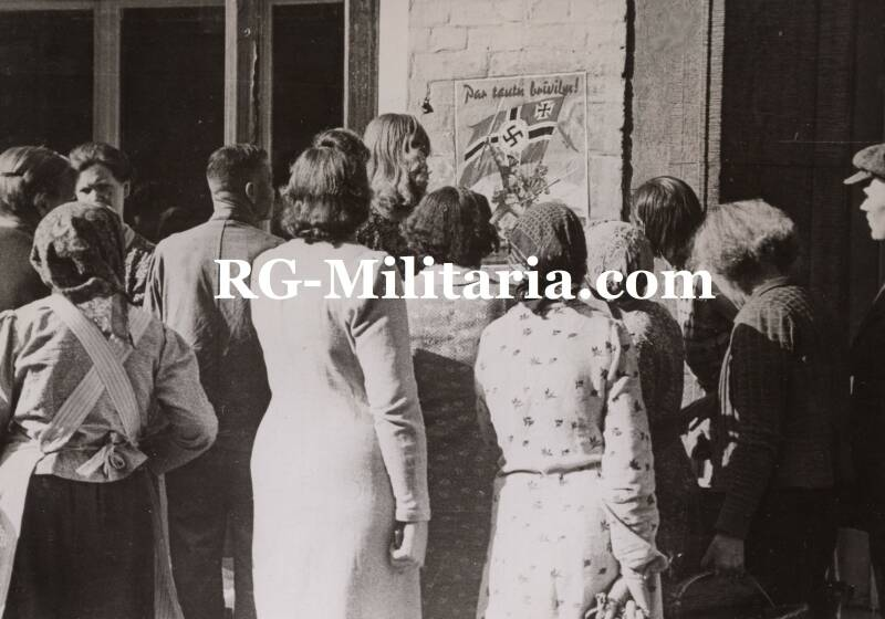 Press photo - Latvian civilians looking at a Wehrmacht volunteers poster (1941)