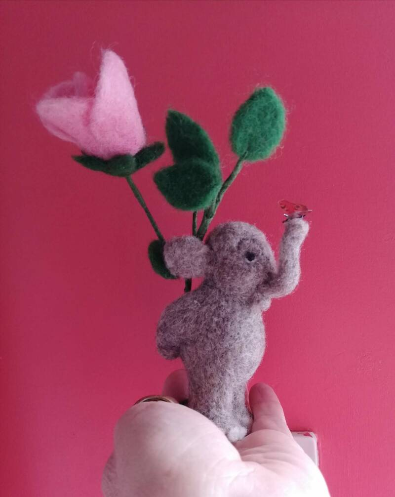 It wasn't me! Little grey elephant with rose.